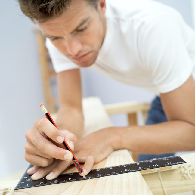 Young Man Measuring a Plank of Wood with a Ruler and a Pencil